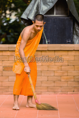 monk sweeping ground chiang mai thailand