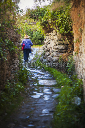 old chinese woman walks up winding