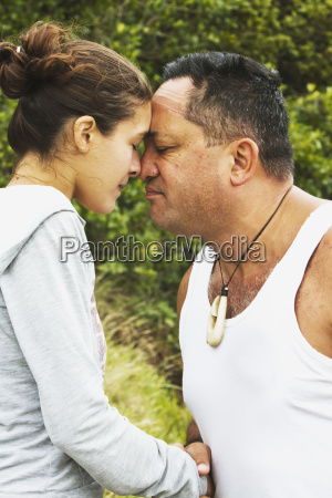 tourists try the traditional maori greeting
