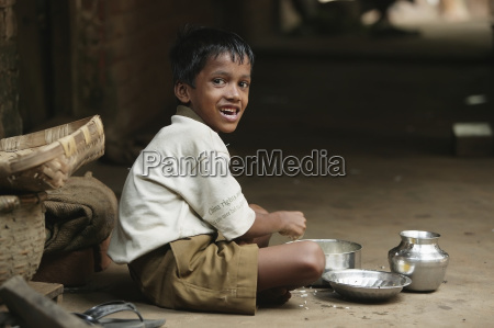 a young boy eats lunch sitting