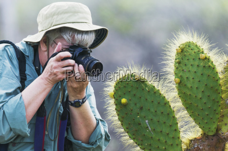 a woman photographs a prickly pear