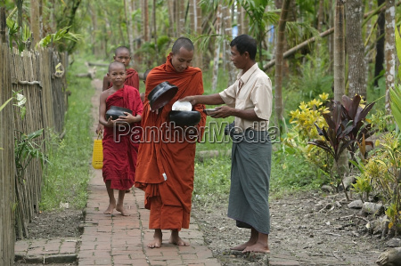 buddhist monks receiving alms from villager