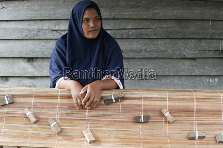 a woman making bamboo blinds in