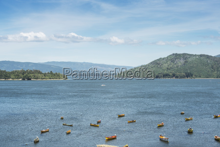 fishing boats with mountains in the