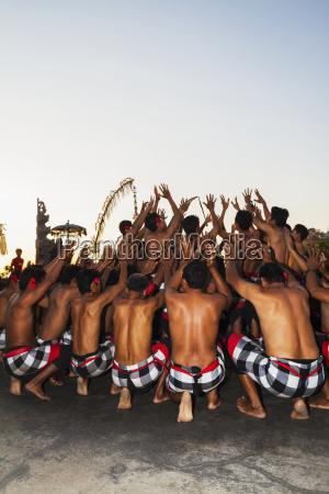men dancing in a circle chanting