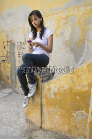 teenage girl texting on cell phone
