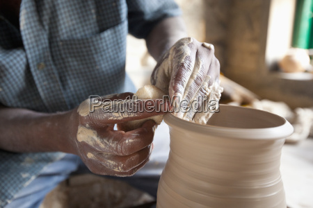a potter forms the clay on
