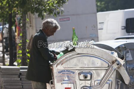 man sifting through a rubbish bin
