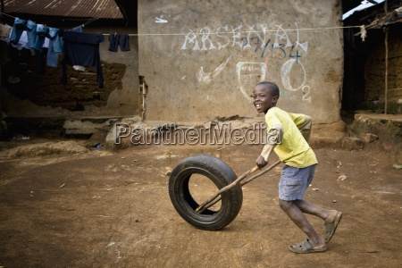 a boy rolls a tire by