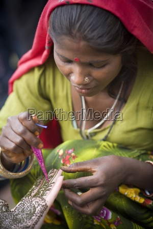 woman practicing henna tattooing delhi india