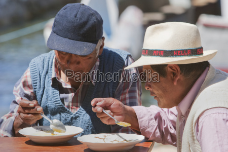 aymara men having lunch on the