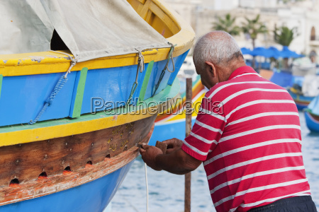 fisherman fixing his luzzu a traditional