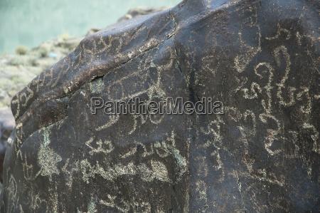 petroglyphs on a boulder show a