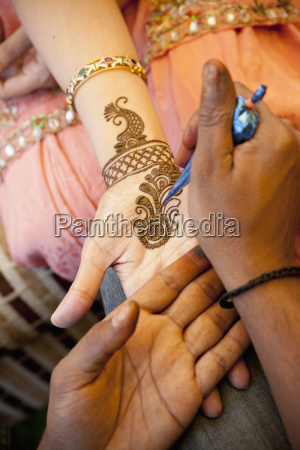 mehndi being put on a womans