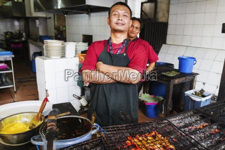 cook barbecuing shrimp at candi gama