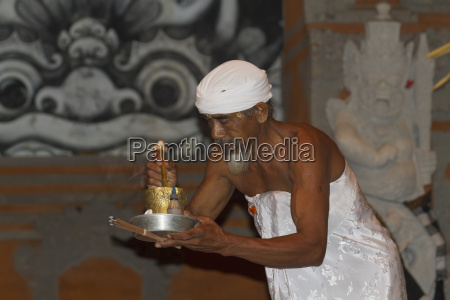priest carrying incense and a flower