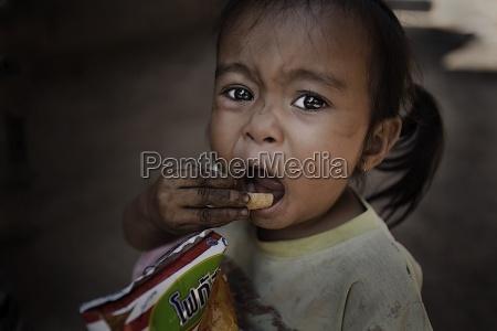young girl eating chips luang prabang