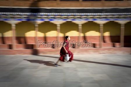buddhist student running through monastery carrying