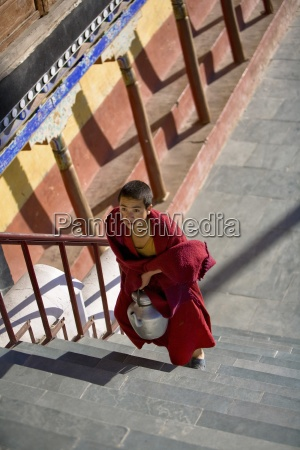 young buddhist student carrying teapot up