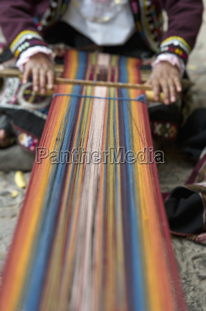 a person weaving colorful fabric cusco