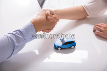 car dealer shaking hands with his
