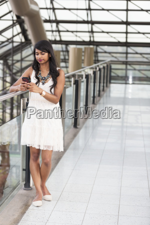 young professional businesswoman texting on her