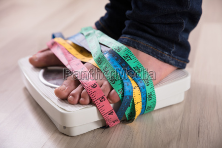 persons feet on weight scale wrapped