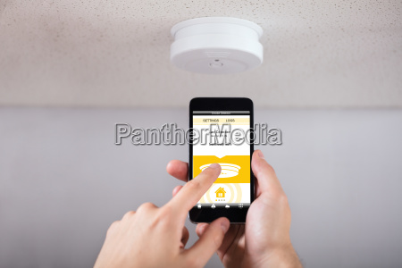 person operating smoke detector with mobile