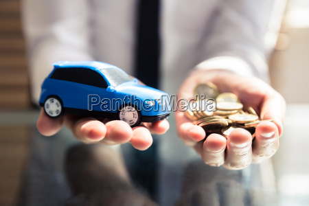 businessperson holding small blue car and