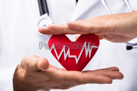 doctor protecting red heart with heartbeat