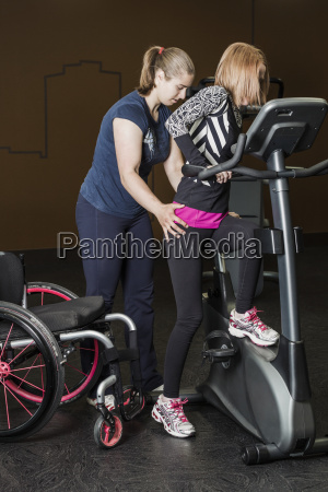 physiotherapist assisting young woman with spinal