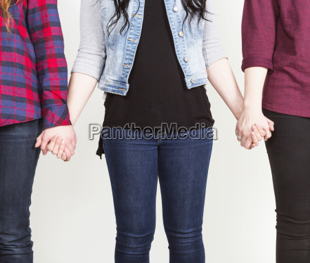 three young women holding hands committed