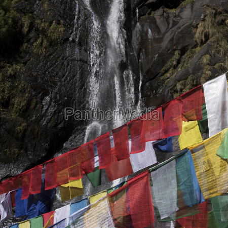 colourful prayer flags and a waterfall