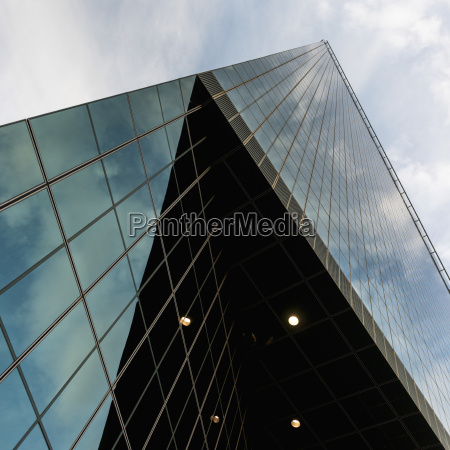 skyscraper with glass walls reflecting the