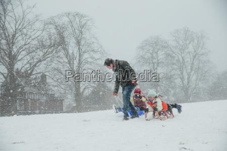 family sledding in the snow