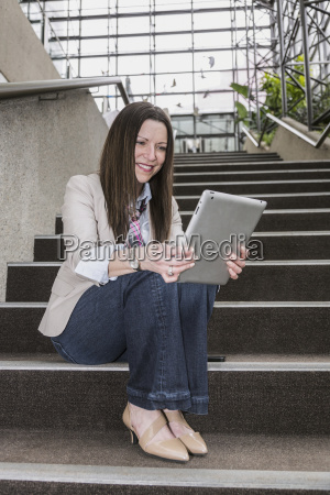mature business woman sitting on stairway
