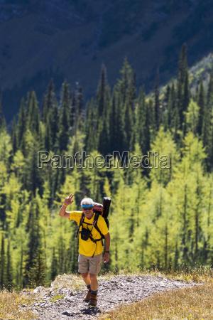 male hiker on mountain trail waving