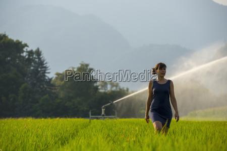 a woman walks through a lush