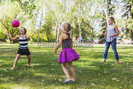mother and daughters throwing a ball