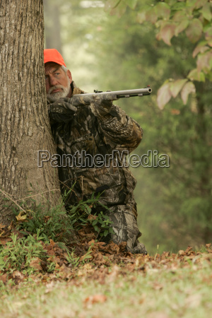 hunter stalking whitetail deer with rifle