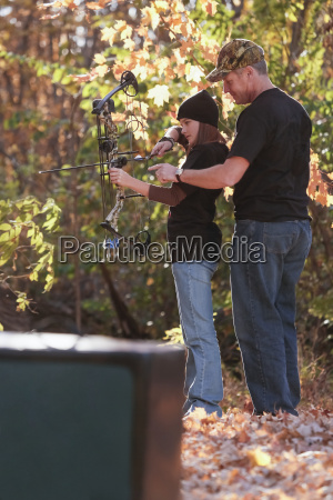 father teaches daughter at archery range