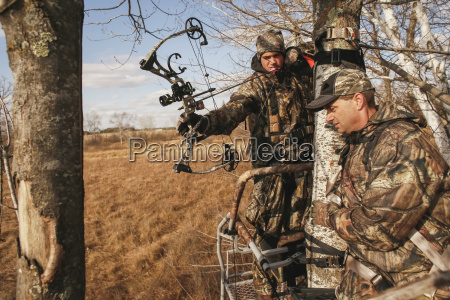father coaches son on bowhunting in
