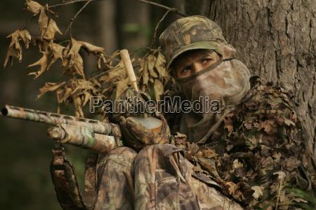 female turkey hunter with shotgun in
