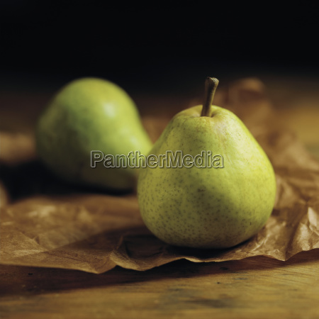 green pears sitting on brown parchment