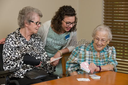 senior citizens and caregiver playing cards