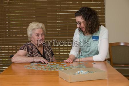 senior citizen and caregiver building a