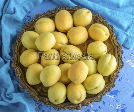 ripe apricots in a copper iron
