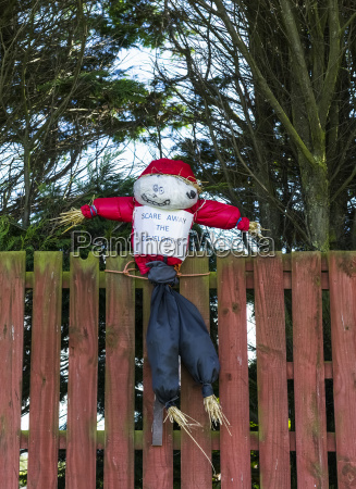 a scarecrow sits on a fence