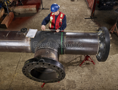 a tradesman measures a pipe for