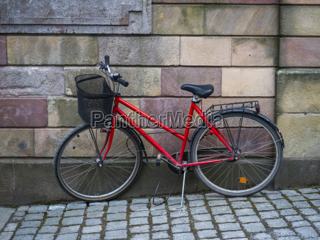 a red bicycle parked against a